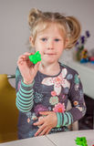 Cute little girl playing with plasticine. At home Stock Photo
