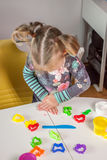 Cute little girl playing with plasticine. At home Royalty Free Stock Images