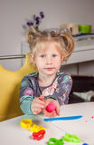 Cute little girl playing with plasticine. At home Stock Photography