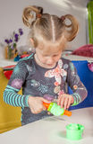 Cute little girl playing with plasticine. At home Stock Images