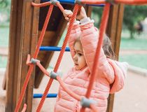 Cute little girl playing on playground. Climbing rope ladder stock photo
