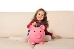 Cute little girl playing puts coin in huge piggy bank on sofa Royalty Free Stock Photos