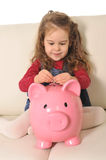 Cute little girl playing puts coin in huge piggy bank on sofa Stock Photos