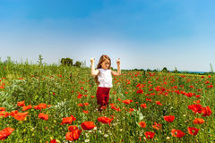 Cute little girl playing in red poppies field summer day, beauty stock photo
