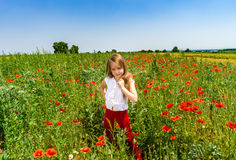 Cute little girl playing in red poppies field summer day, beauty Royalty Free Stock Photos