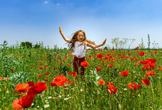 Cute little girl playing in red poppies field summer day, beauty royalty free stock image