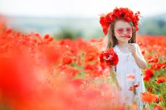Cute little girl playing in red poppies field summer day beauty and happiness France. A small pre-school girl with long curly hair, dressed in a white sleeveless royalty free stock photos