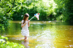 Cute little girl playing in a river catching rubber ducks with her scoop-net Royalty Free Stock Images