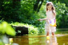 Cute little girl playing in a river catching rubber ducks with her scoop-net Stock Photos