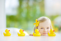 Cute little girl playing with rubber ducklings at home Stock Photos