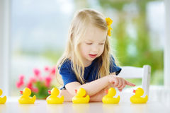 Cute little girl playing with rubber ducklings at home Stock Photography
