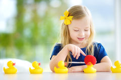Cute little girl playing with rubber ducklings at home Royalty Free Stock Photography