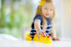 Cute little girl playing with rubber ducklings at home Royalty Free Stock Photos