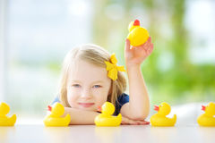 Cute little girl playing with rubber ducklings at home Stock Photo