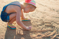 Cute little girl playing with sand on the beach Royalty Free Stock Images