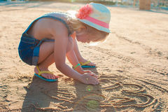 Cute little girl playing with sand on the beach Royalty Free Stock Photos
