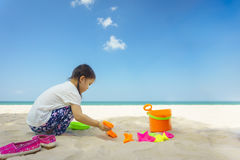 Cute little girl playing with sand on the beach Royalty Free Stock Photo