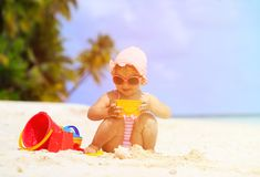 Cute little girl playing with sand on the beach Royalty Free Stock Photography