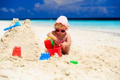 Cute little girl playing with sand on the beach Stock Photos