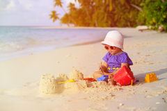 Cute little girl playing with sand on beach Stock Image