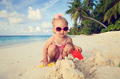 Cute little girl playing with sand on beach. Cute little girl playing with sand on tropical beach Stock Photos