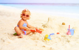 Cute little girl playing with sand on beach. Cute little girl playing with sand on tropical beach Royalty Free Stock Images