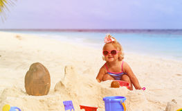 Cute little girl playing with sand on beach Stock Photos
