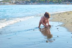Cute Little Girl playing with sand by the Sea Waves. Summer Sun stock image