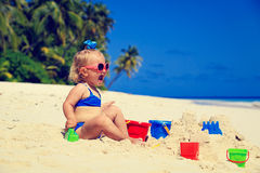 Cute little girl playing with sand on tropical Stock Photos