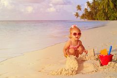 Cute little girl playing with sand on tropical Royalty Free Stock Images
