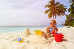 Cute little girl playing with sand on tropical Royalty Free Stock Photos