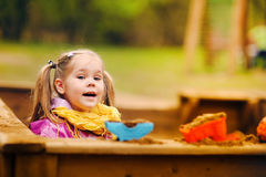 Cute little girl playing in a sandbox Stock Images