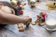 Cute little girl is playing with Santa`s cookies and milk at Chr royalty free stock photography