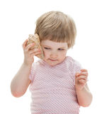 Cute little girl playing with a seashell Stock Image