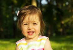 Cute little girl is playing on send in sunny day Stock Image