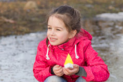 Cute little girl playing with ship in the spring creek standing in water Royalty Free Stock Images