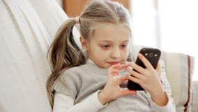 Cute little girl playing with smartphone at home