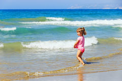Cute Little girl is playing in the spray of waves at sea on a su Stock Image