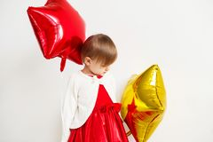 Cute little girl playing with star shaped balloons in front of w Royalty Free Stock Photos