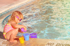 Cute little girl playing in swimming pool at beach Stock Image