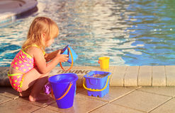 Cute little girl playing in swimming pool at beach Stock Photos