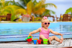 Cute little girl playing in swimming pool at beach Royalty Free Stock Images