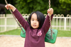 Cute little girl playing swing Stock Images