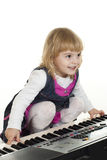 Cute little girl playing on a synthesizer Royalty Free Stock Images