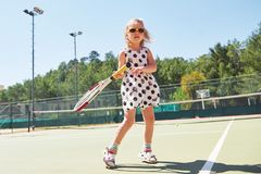 Cute little girl playing tennis on the tennis court outside Royalty Free Stock Images