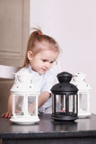 Cute little girl playing with three luminaires with candle Royalty Free Stock Photos