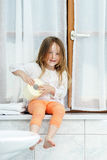 Cute little girl playing with toilet paper roll Royalty Free Stock Image