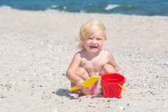Cute little girl. Playing with toy buckets and spade in sand on sea beach Royalty Free Stock Photo
