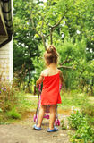 Cute little girl is playing with toy carriage in the park Stock Photo