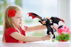 Cute little girl playing with toy dragon Royalty Free Stock Photo